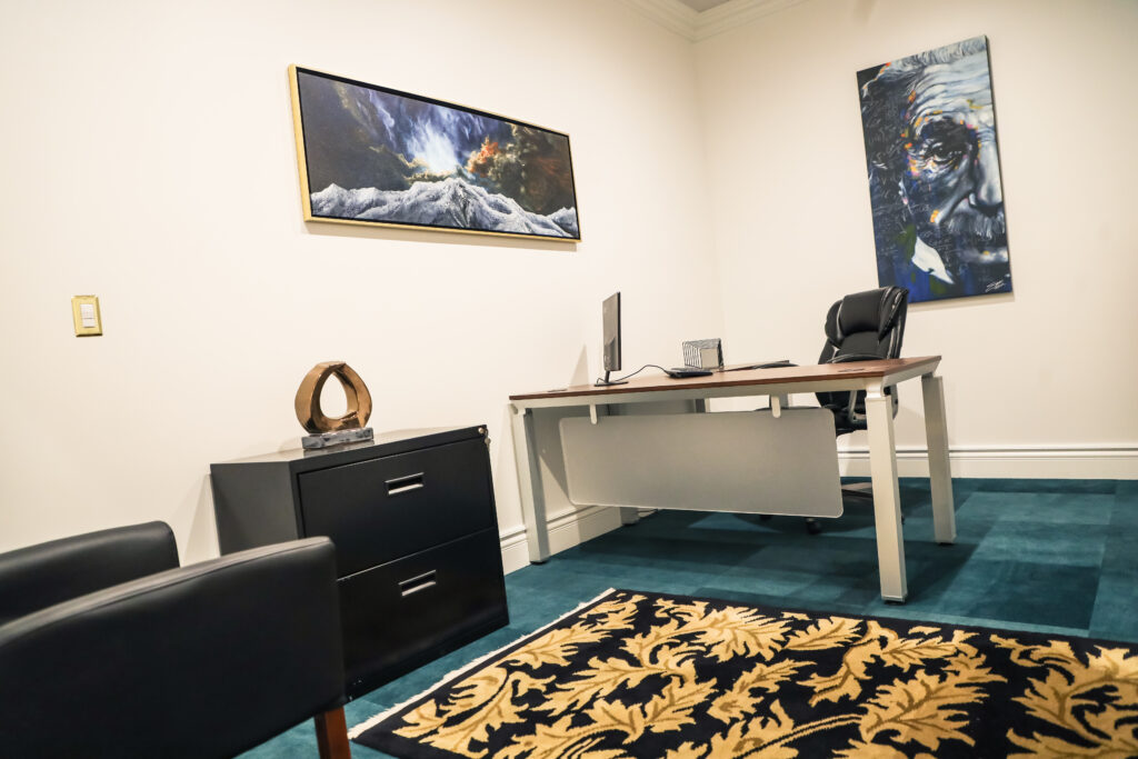 An office space with a single desk in it that when leasing, you should ask questions about.